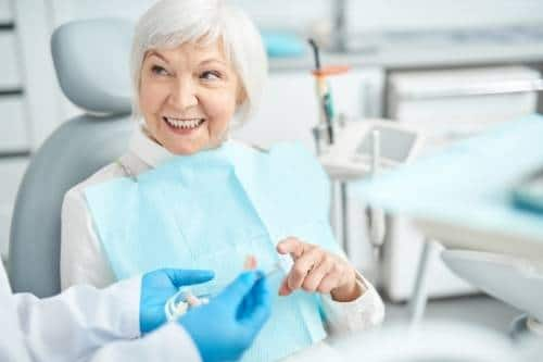 A senior woman visiting the dentist prepared with her dentist checklist