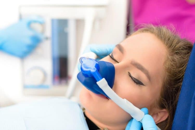 Woman being administered a sedative during a dental appointment