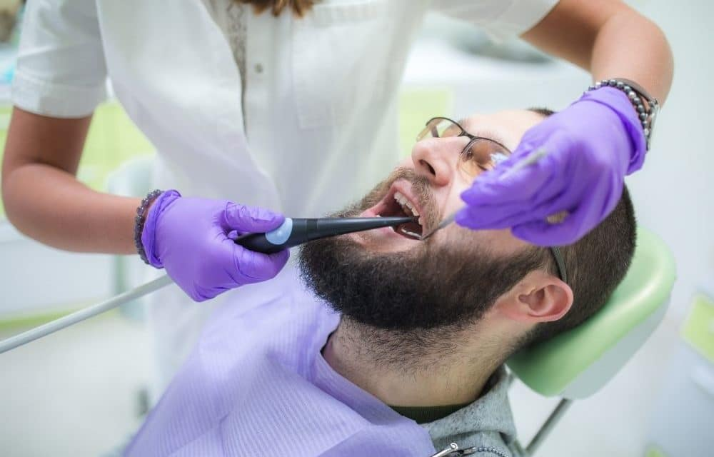 Man laying in the dentist seat getting cavities removed